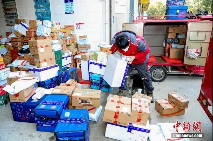 2月9日,武汉汉口将军路一家快递公司的快递点,快递员们收拾到站的快件。新冠肺炎疫情之下,大批民众挑选线上购物,快递员比平常更繁忙。中新社记者 张畅 摄