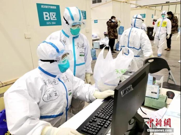 """图为武汉客厅""""方舱医院""""里的医护人员。中新社发 高翔 摄"""