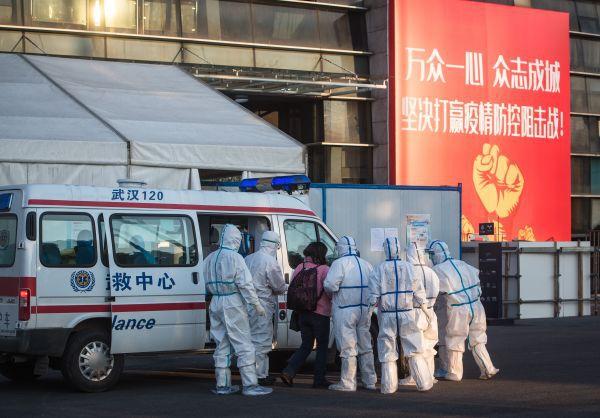 ▲2月12日,医护人员将患者送入武汉体育中心方舱医院。(新华社)