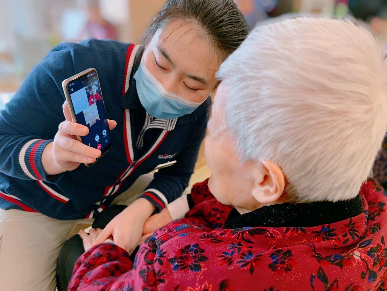 西钓鱼台一养老院,护理员协助老人经由过程视频通话手段与家属说相符。受访者供图