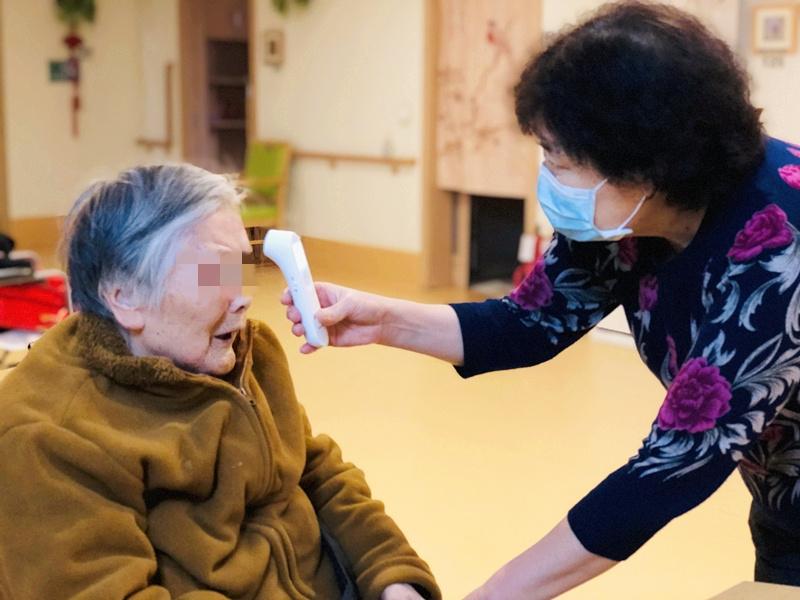 养老院封闭后,院长于金秀添入到一线护理走列,为老人进走每日体温测量是做事内容之一。受访者供图