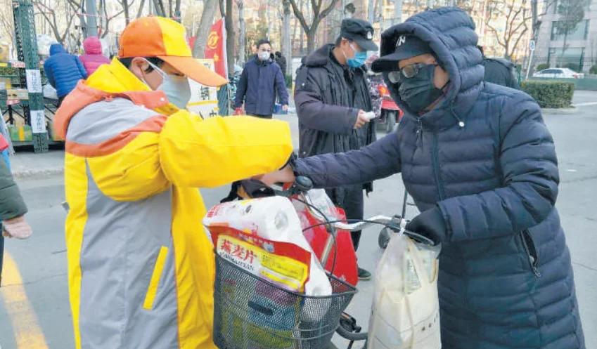 △北京的志愿者在社區進出口監測來往人員體溫。