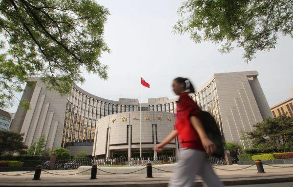 行人从北京中国人民银行大楼前经过。(新华社)