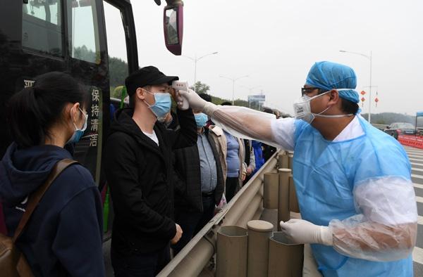 2月1日,在南宁东高速公路收费站附近,工作人员为进城大巴上的乘客测量体温。 新华社记者 陆波岸 摄
