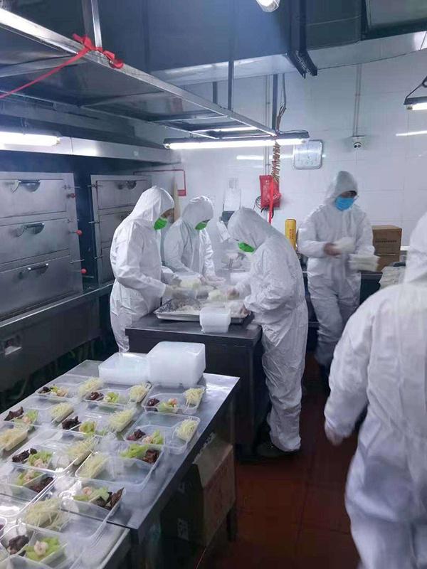 餐饮部门工作人员身着防护服为医护们准备餐食