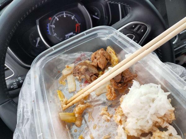 志愿者在车上吃盒饭。