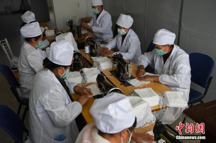2月3日,自愿者们自带缝纫机无偿制作棉纱医用口罩。云南省安和市60名自愿者在疫情期间无偿生产棉纱医用防护口罩以缓解市场资源紧缺。中新社记者 康平 摄
