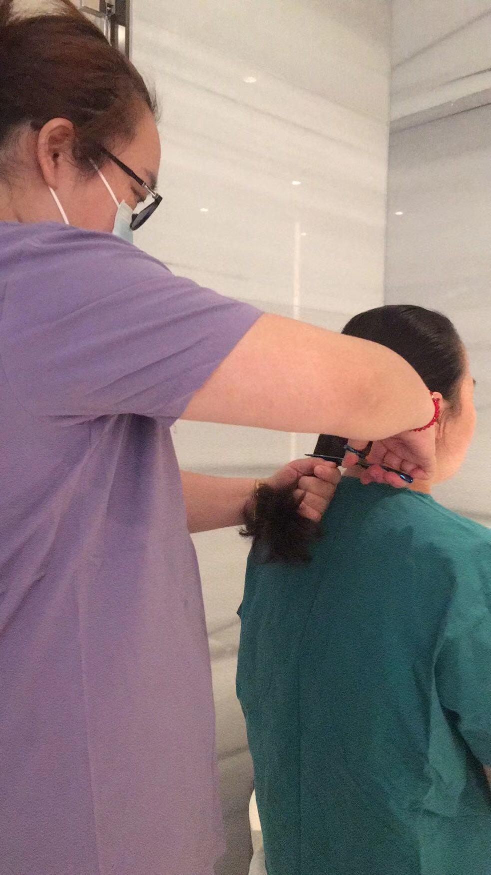 长发难打理、容易污染,查琼芳在医护人员的帮助下理发。本文图均为 查医生 供图
