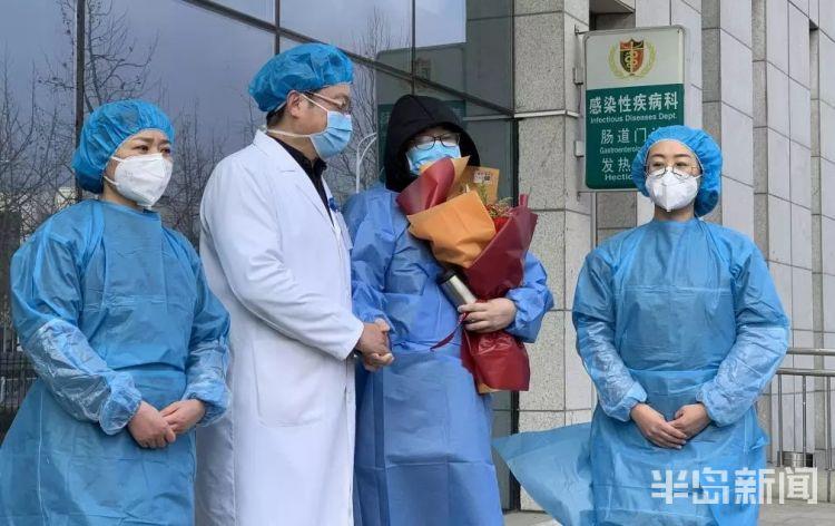 青岛市医疗专家组组长孙运波与张阳握手交谈,庆祝其出院。