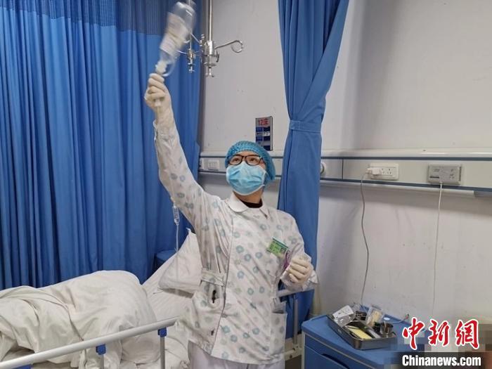图为杜富佳在给患者更换药品。 湄潭县融媒体中心供图