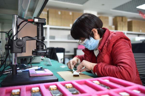 不息复工的企业采取多项措施确保防疫复工两不误。图为2月24日,北京一家公司员工在清洗体温筛查仪中央组件。(陈钟昊 摄)