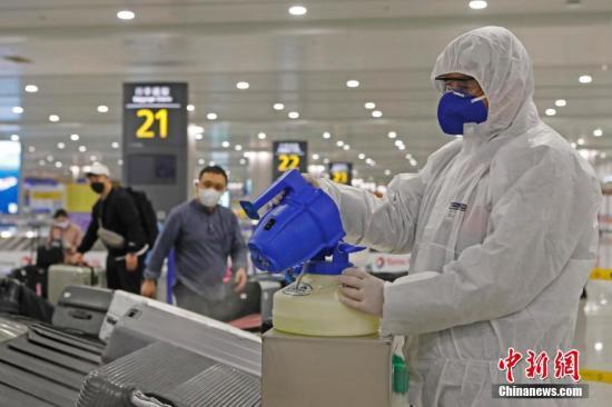 资料图:工作人员对入境旅客行李进行消毒。 中新社记者 殷立勤 摄