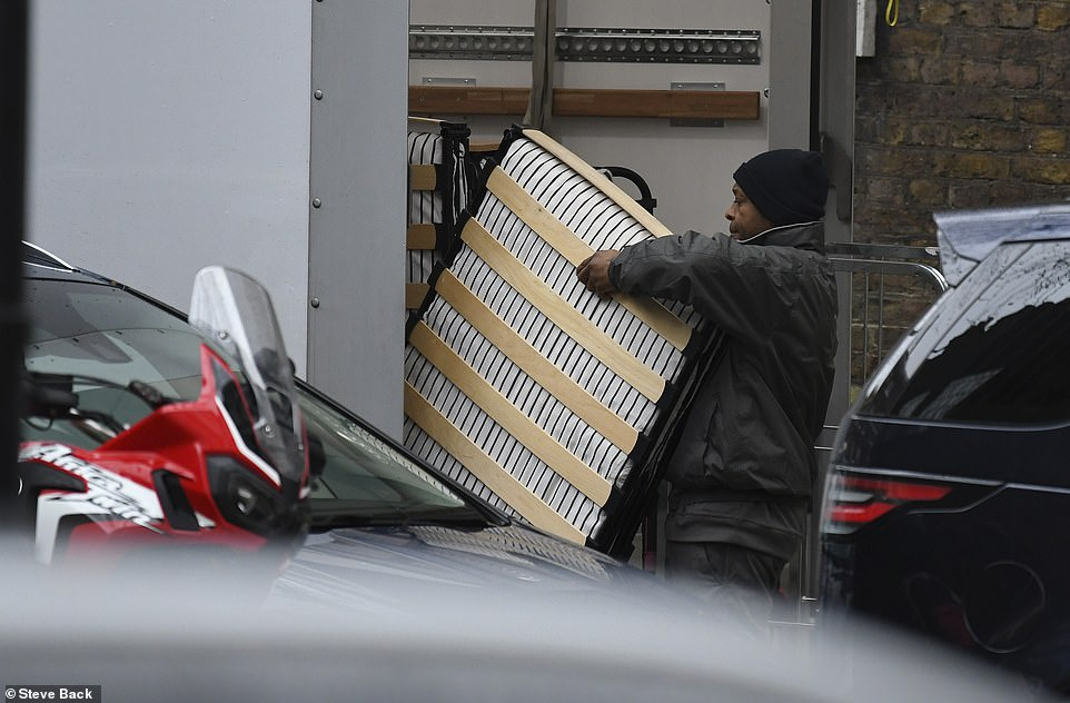 Workers remove folding beds from trucks (Image: Daily Mail)