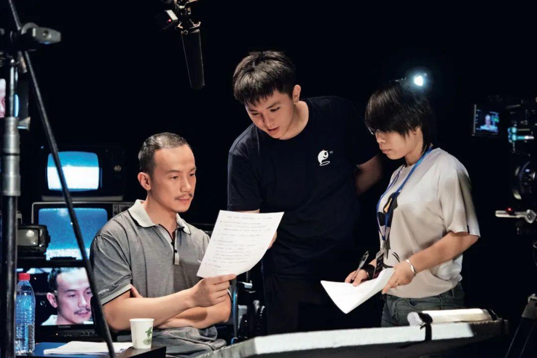 《不思异:录像》的拍摄现场:导演欧丁丁(中)与演员孙一明(左)疏导剧本。图/受访者挑供