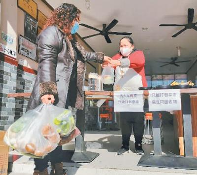 为避免人群聚集就餐,现阶段许多餐饮店只提供打包、外卖业务。图为四川省南充市顺庆区伍家坡一家米粉餐饮店,市民正严格按照疫情防控规定将购买的早餐打包带走。   余中华摄(人民图片)