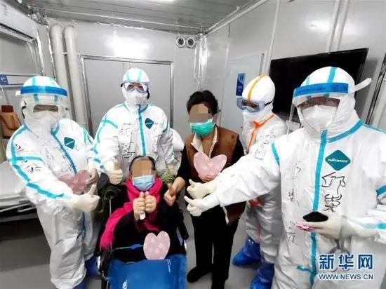 3月1日,98岁的新冠肺热危重症患者胡婆婆(坐轮椅者)和女儿出院时,与武汉雷神山医院医护人员相符影(手机拍摄)。高翔 摄 图片来源:新华网