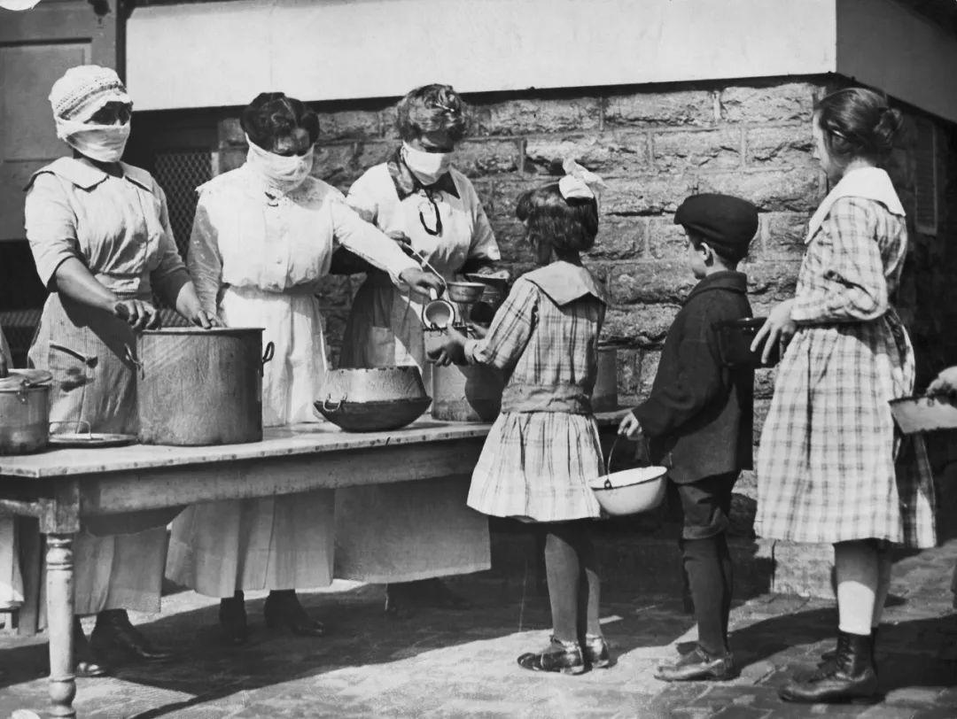 ▲资料图片:1910年代,美国辛辛那提,在流感大爆发期间,志愿者们都戴着口罩给孩子们发放食物。