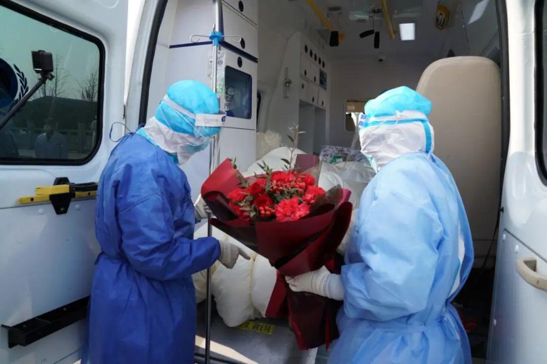 医护人员将百岁患者送上转运车辆 摄影:高辉