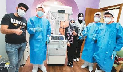 中国红十字会总会援助伊拉克防治新冠肺炎医疗专家组成员,在成功安装移动X光机后与当地医务人员合影。新华社发