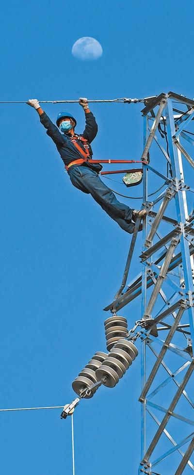 4月4日,在安徽省亳州市谯城区,国网亳州供电公司电力工人正在架设输电线路。 张延林摄(影像中国)