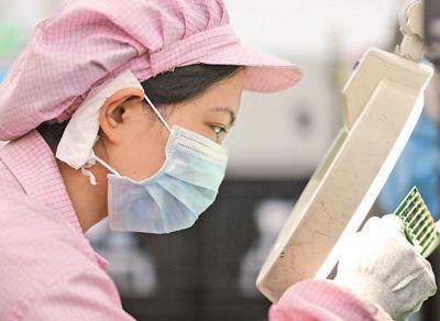 3月31日,在中国信科集团烽火通信公司系统设备制造部的5G智造车间,工人正在生产相关设备。 人民日报记者 李 舸摄