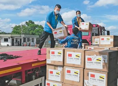 4月23日,中国政府向文莱政府捐助并移交了一批抗疫物资。图为工作人员搬运中国政府捐助的抗疫物资。 新华社发