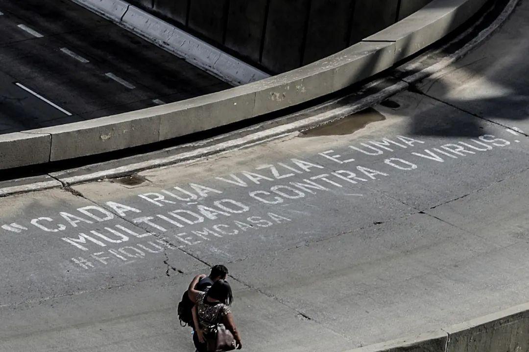 """4月21日,巴西圣保罗市一条道路上写有""""对于抗击病毒来说街道太拥挤了 #待在家中""""字样。新华社发"""