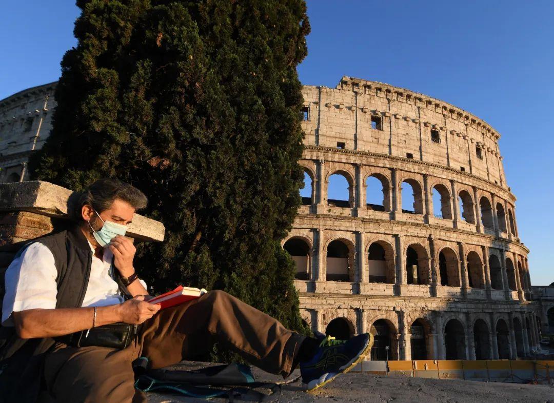 4月26日,一名戴着口罩的男子在意大利首都罗马的斗兽场附近看书。新华社发