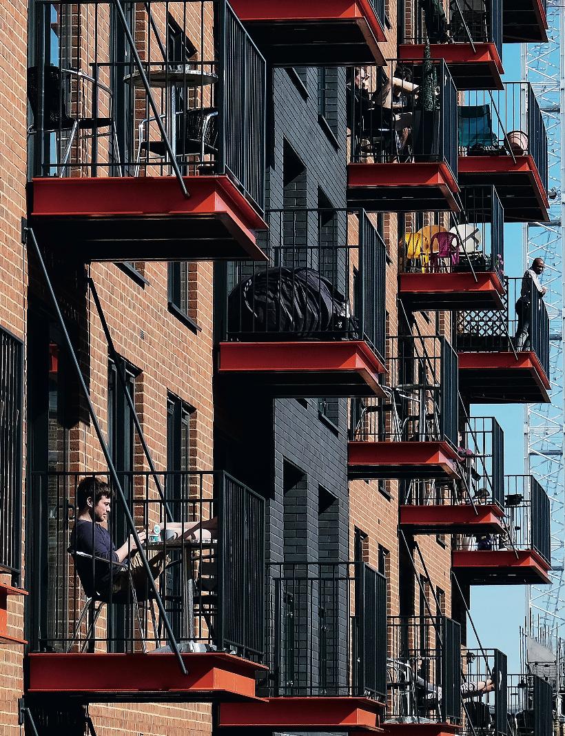 4月4日,在英国伦敦,人们在阳台上享福阳光。图/路透