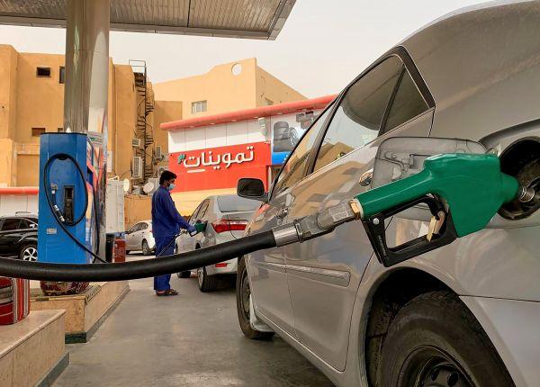 5月11日,在沙特阿拉伯利雅得,一名加油站工作人员给汽车加油。(新华社)