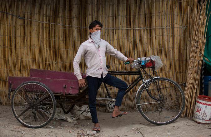 5月13日,在处于封锁状态的印度首都新德里,别名外子站在三轮车旁(图片来源:新华社 贾伟德·达尔 摄)