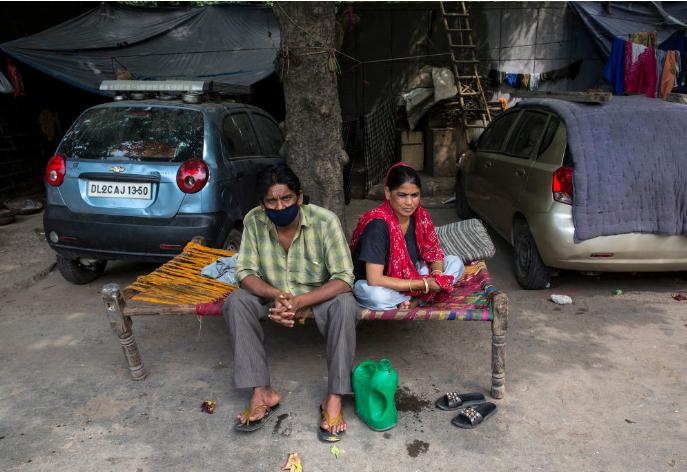 5月13日,在处于封锁状态的印度首都新德里,一对夫妇坐在路边(图片来源:新华社贾伟德·达尔摄)