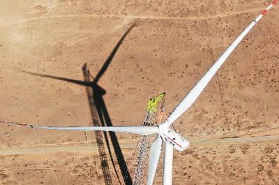 图为5月1日,在青海省海南州共和县的国家电投黄河公司风力发电项目建设现场,风力发电机组在吊装。新华社记者 张宏祥摄