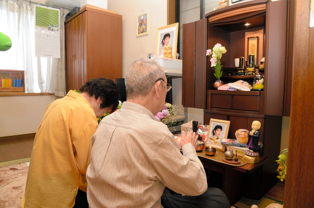 石田奈央美的父母坐在孩子的佛坛前(朝日新闻)