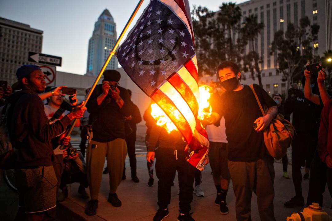 △示威者点燃美国国旗 图片来源:《洛杉矶时报》