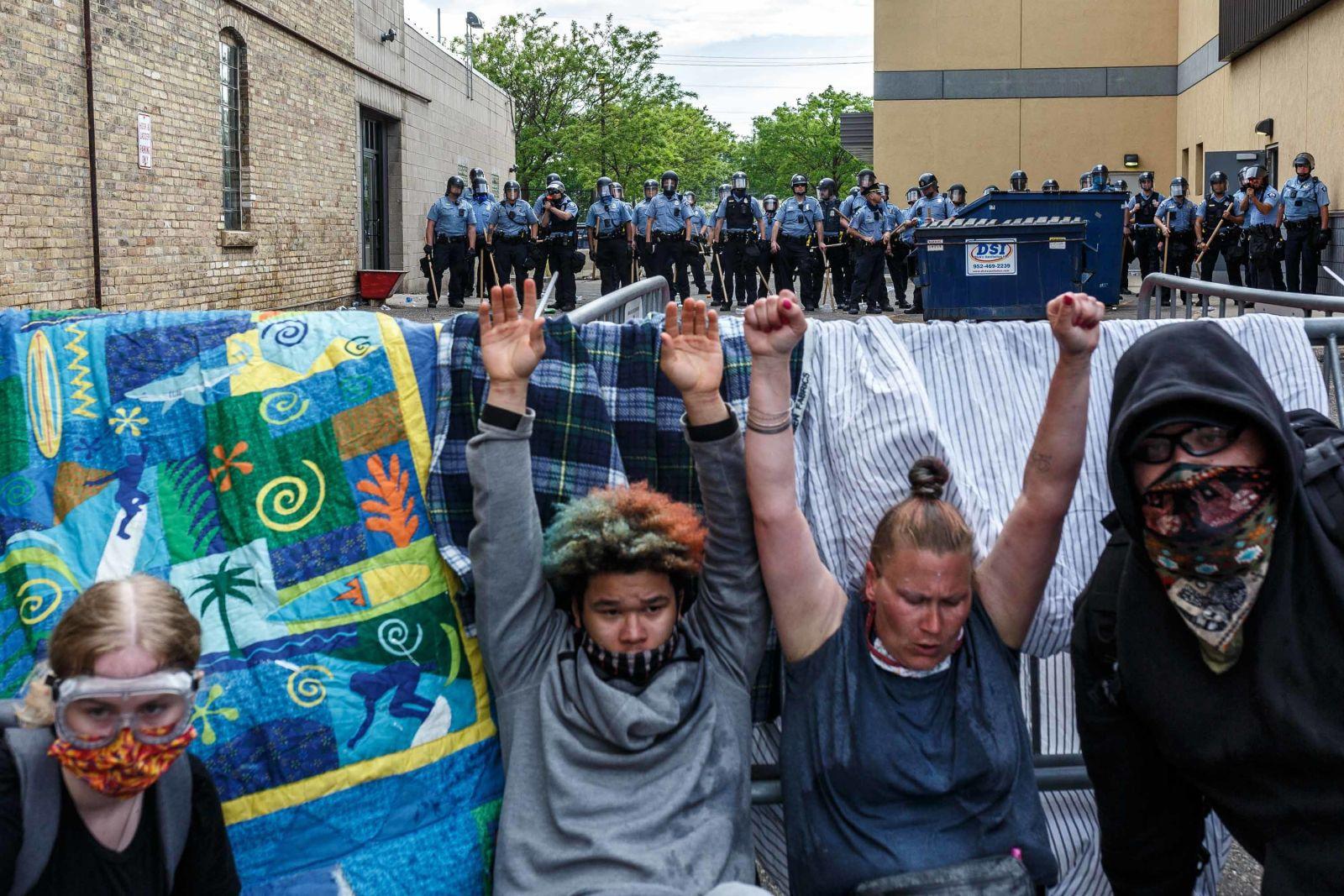 27日在明尼阿波利斯,面对警察,抗议者举起双手。(法新社)