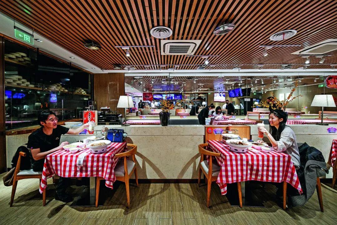 3月11日,一对情侣在天津大悦城内一家餐厅隔桌而坐就餐。当日,天津片面商场恢复业务,运营期间将不中止地进走公共区域高频准时消毒并限定客流。摄影/本刊记者 佟郁