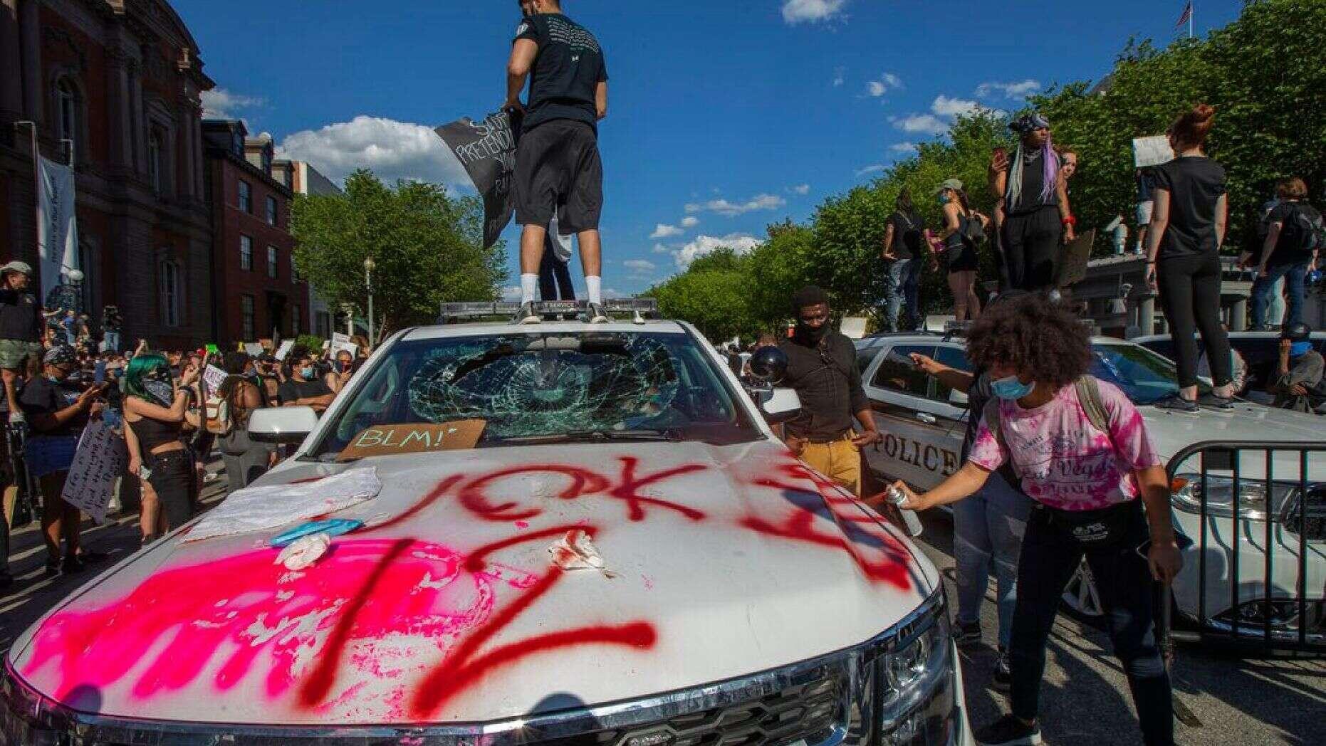 5月30日,在白宫附近,示威者站在的美国特勤局车辆上,车辆挡风已玻璃破碎(图源:美联社)