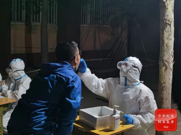 图为医护人员正在进行咽拭子采样。