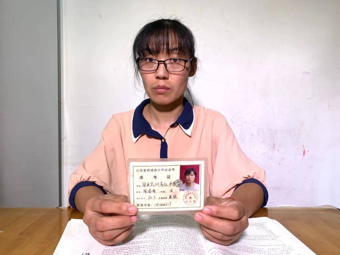 陈春秀举着16年前高考时的准考证