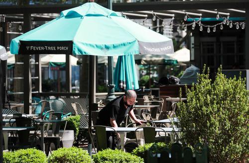 6月22日,在美国纽约布莱恩特公园,别名餐厅做事人员在户外就餐区做准备。新华社记者 王迎 摄