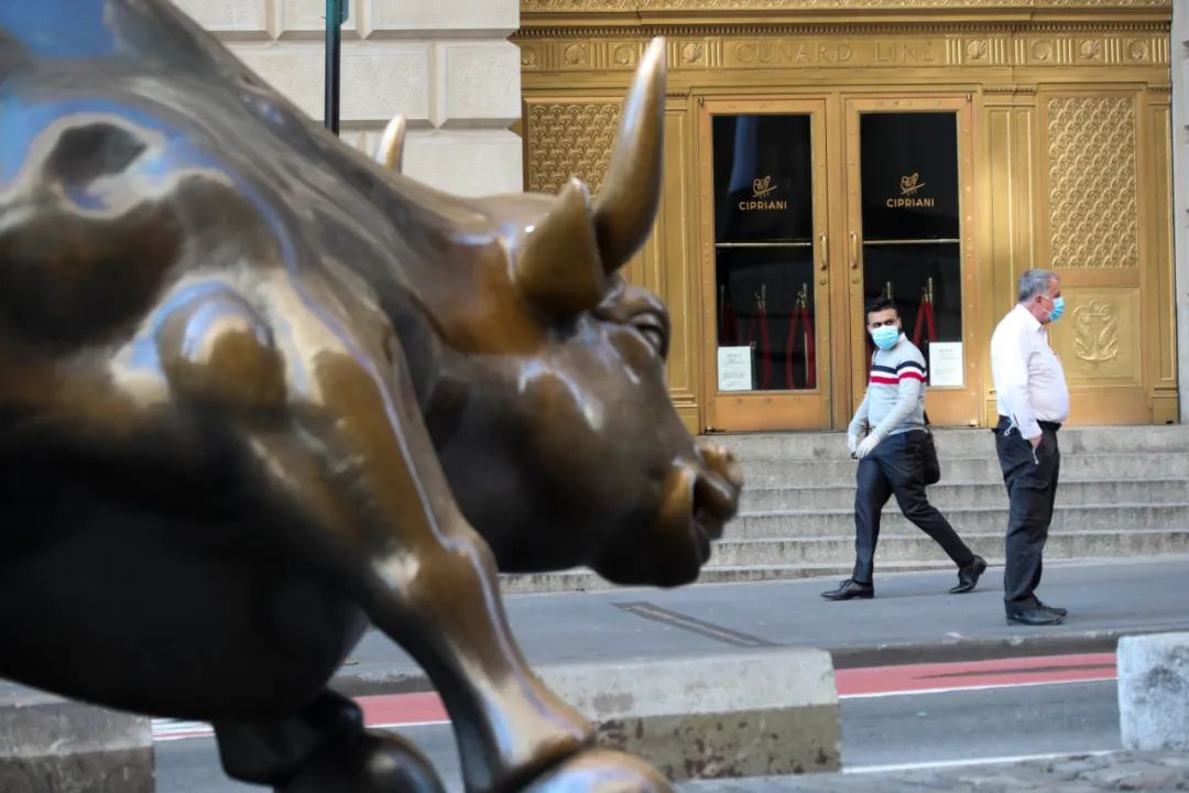 3月24日,在美国纽约曼哈顿下城,戴口罩的外子从华尔街铜牛旁路过。新华社记者 王迎 摄