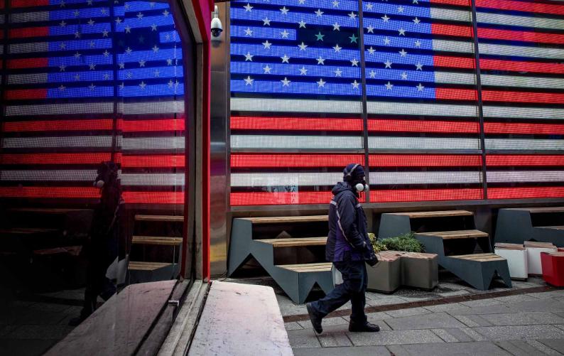 △别名美国快递员工佩戴着口罩走过时代广场(图片来源:彭博社)