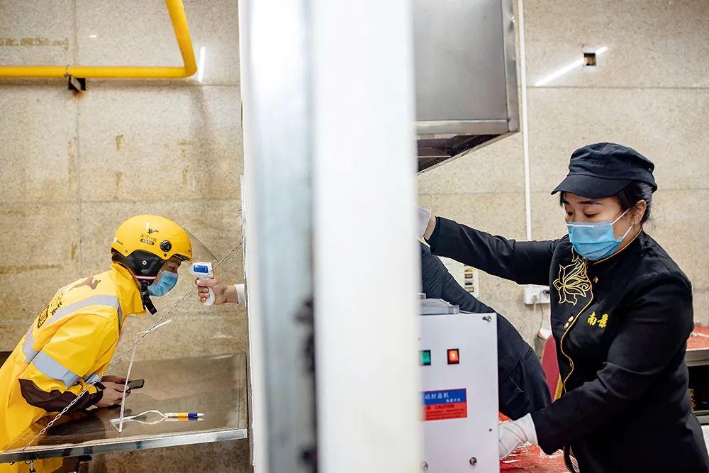 2月14日,湖南长沙市的一处外卖站点,外卖小哥赶来后首先做的是检测体温、酒精消毒,然后再取餐、外送。图/人民视觉