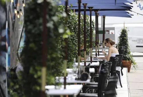 7月30日,在美国纽约苏豪商业区,人们在餐厅户外就餐区用餐。新华社记者王迎摄