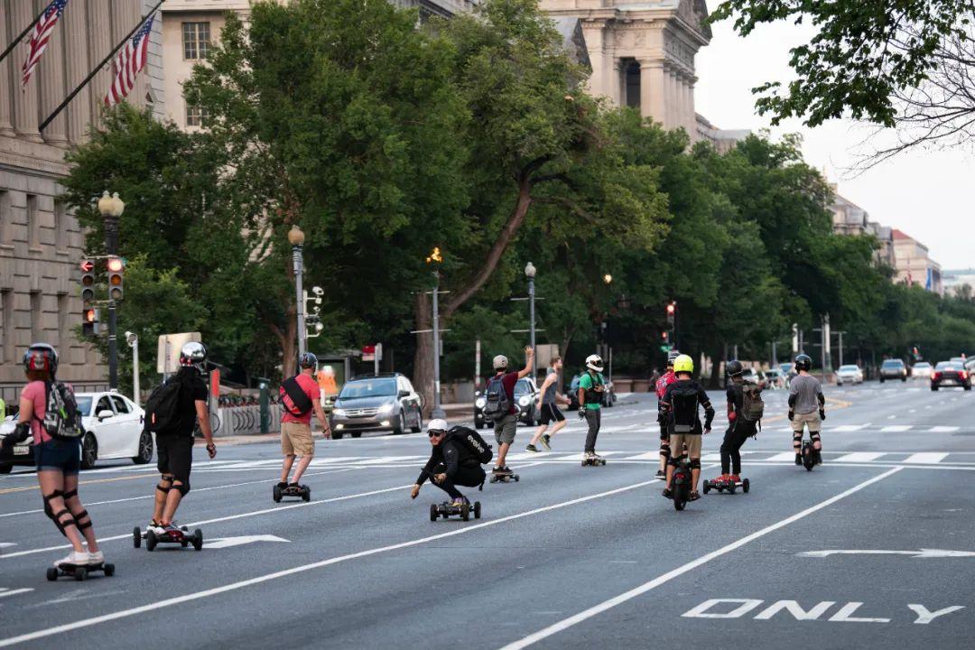 8月5日,一些玩滑板的年轻人在美国华盛顿宪法大道的机动车道上行进。新华社记者 刘杰 摄