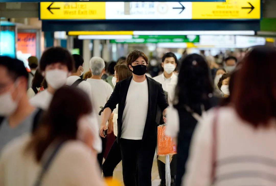 7月9日,在日本东京池袋车站,人们戴口罩出行。新华社/欧新