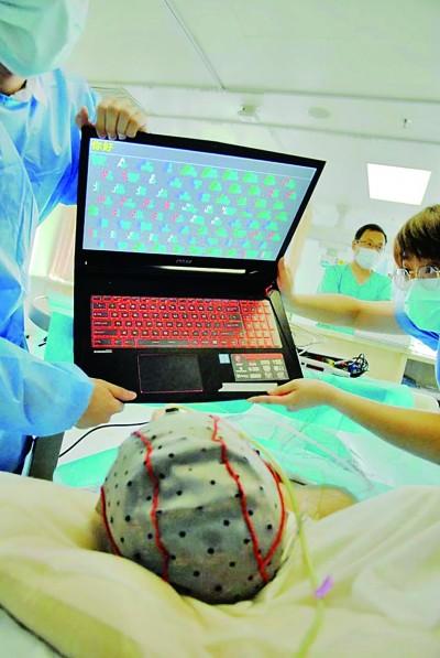 """脑机接口,让失语患者""""说""""出""""你好""""   西安交大二附院的医生给患者进行BCI测试。资料图片"""