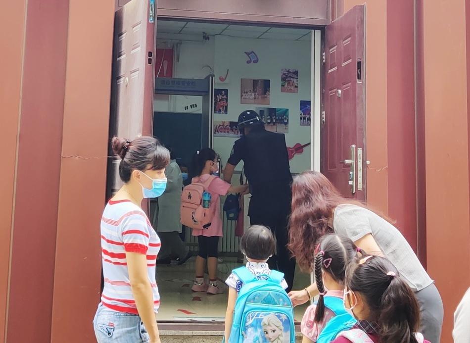 北京十八中附属实验小学的新生们排队等待手部消毒、测体温进校。