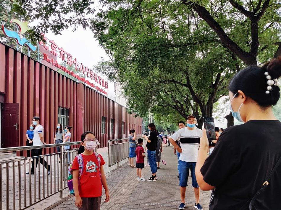 8月29日早上,北京十八中附属实验小学一名新生在校门口拍照留念。本文图片 澎湃新闻记者 程婷